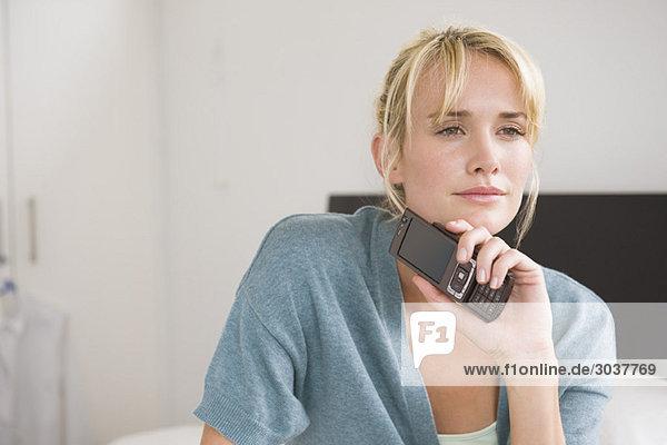 Frau hält ein Handy in der Hand und denkt nach