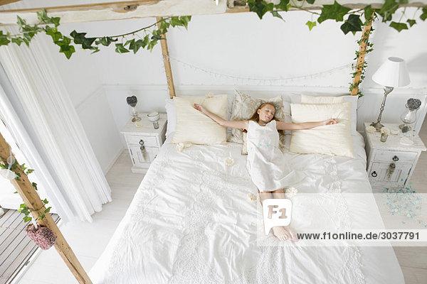 Hochwinkelansicht eines auf dem Bett schlafenden Blumenmädchens