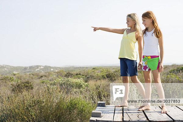 Zwei Mädchen  die auf einer Promenade stehen.