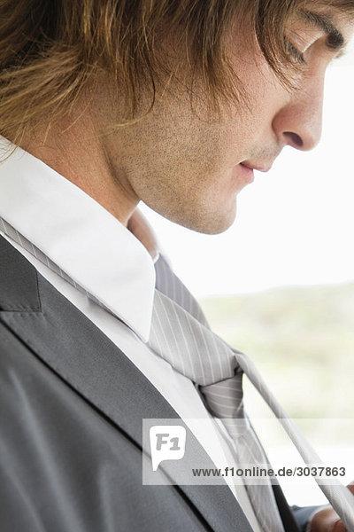 Nahaufnahme eines Bräutigams  der seine Krawatte anpasst.