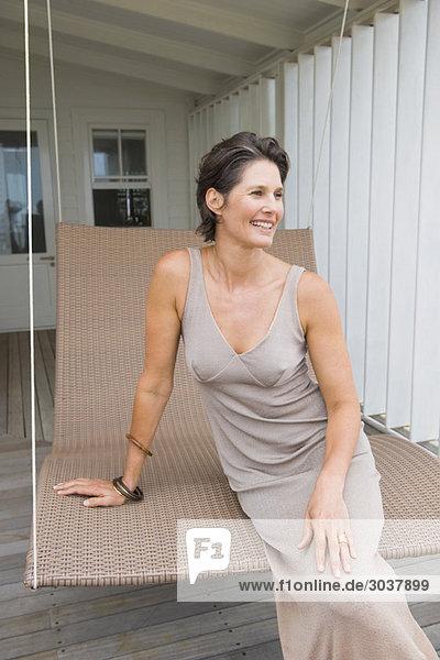 Frau auf der Veranda sitzend und lächelnd