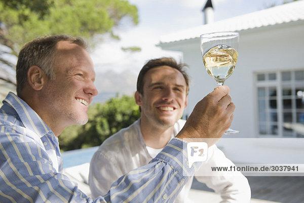 Zwei Freunde beim Betrachten eines Weinglases