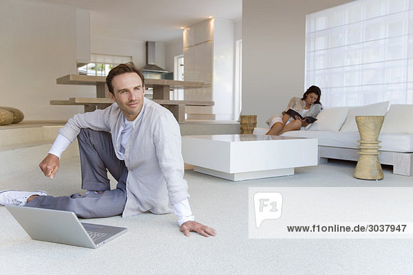 Man sitting on the floor with his wife reading a book in the background