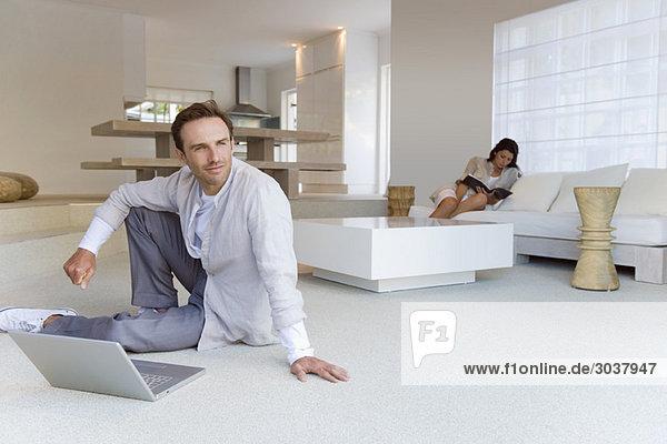 Mann sitzt auf dem Boden und seine Frau liest ein Buch im Hintergrund.