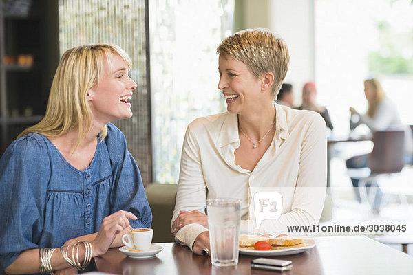 Zwei Frauen  die in einem Restaurant sitzen und lächeln.