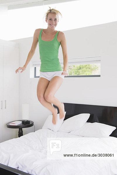 Frau beim Springen auf dem Bett