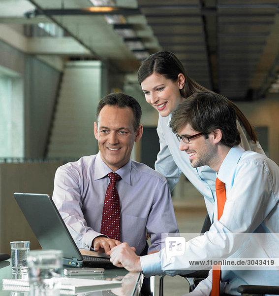 Drei Geschäftsleute suchen auf dem Laptop