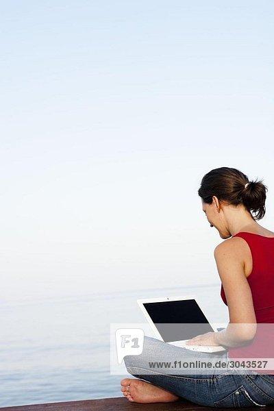 Junge Frau am Steg schaut auf Laptop