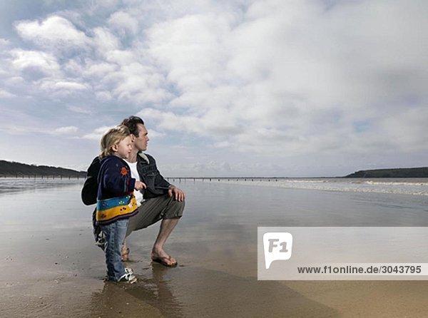 Mann und Kind mit Blick aufs Meer am Strand