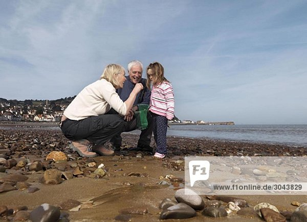 reifes Paar mit Kind am Strand
