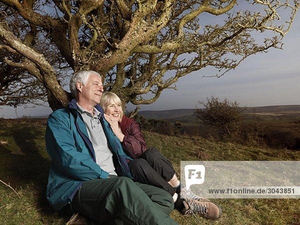 mature couple sitting against tree