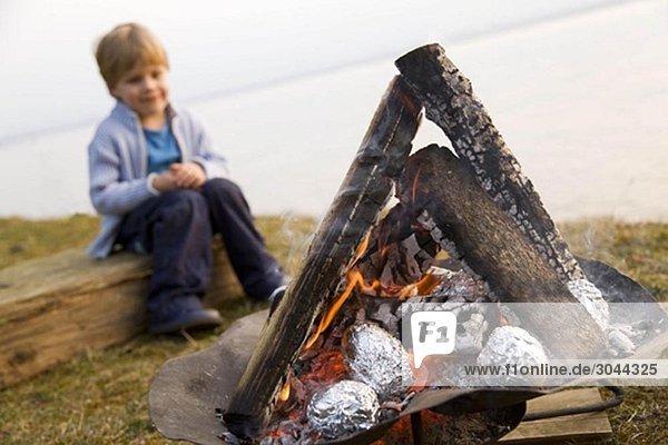 Junge schaut Kartoffeln an Grillfeuer