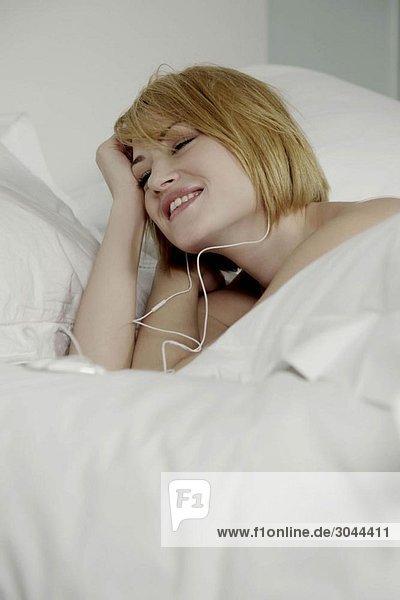 Frau liegt im Bett und trägt Kopfhörer.