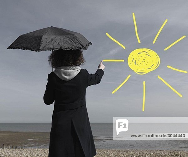 Frau malt Sonne auf grauen Himmel