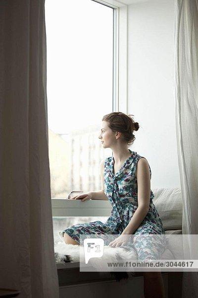 Frau  die aus dem Fenster schaut.