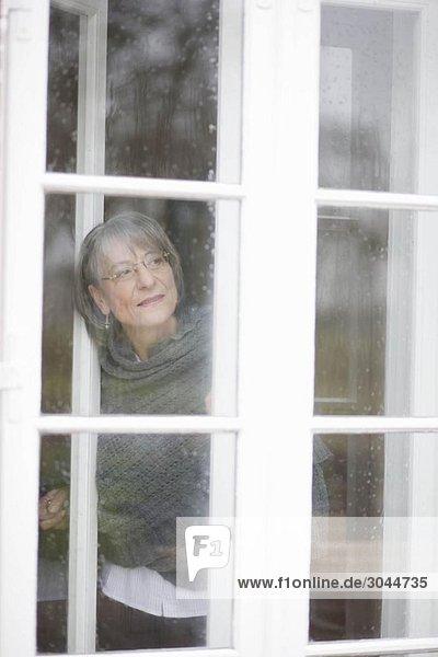 alte Frau  die aus dem Fenster schaut