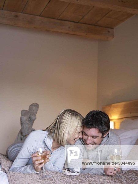 Frau und Mann lächelnd auf dem Bett liegend