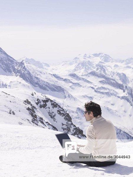 man sitting in the snow using laptop