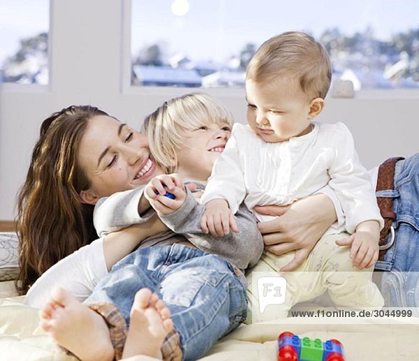 Mutter und Kinder kuscheln und spielen