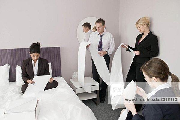 Ein Business-Vierer liest Computerpapier.