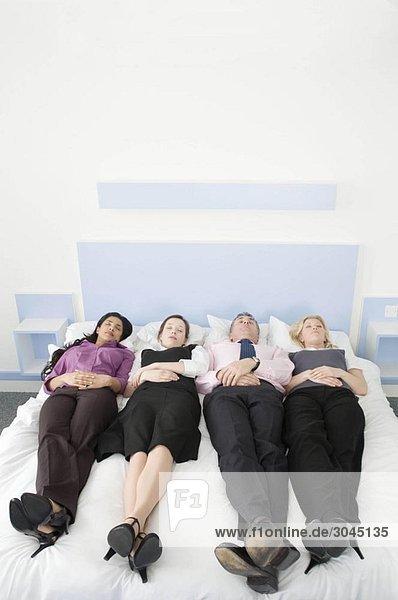 Vier Geschäftsleute im Bett liegend