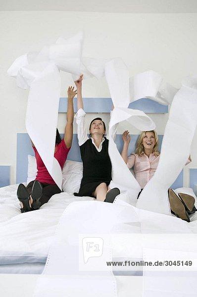 Drei Kolleginnen beim Papierwerfen