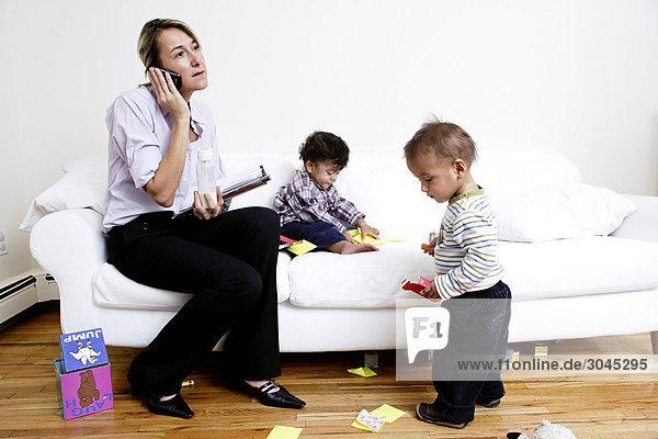 Mutter sitzt auf Sofa sprechen auf Handy während Kinder spielen