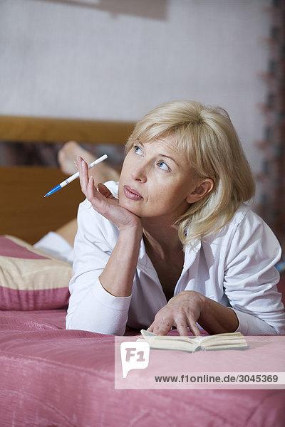 Porträt von Frau liegen auf dem Bett Blick auf Tagebuch