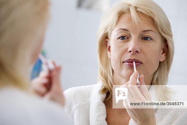 Frau vor Anwendung falmmen Spiegel