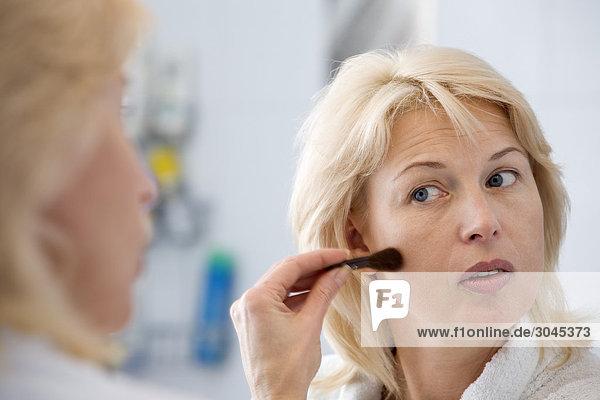 Frau vor Anwendung Make-up mirror