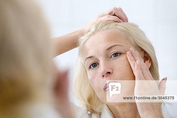 Frau vor Spiegel anwenden von Haut-Creme