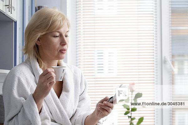 Porträt von Frau im Bademantel Kaffee zu trinken und Überprüfung Handy für Text-Nachrichten