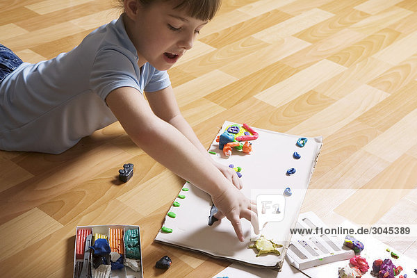junges Mädchen auf Boden spielen mit Modellierung Clay liegen