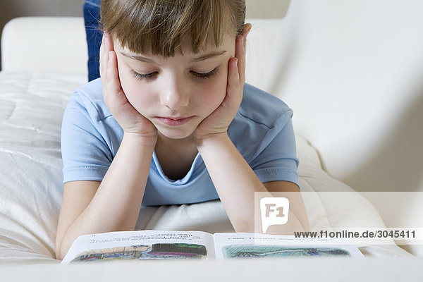 portrait of young girl on sofa reading book