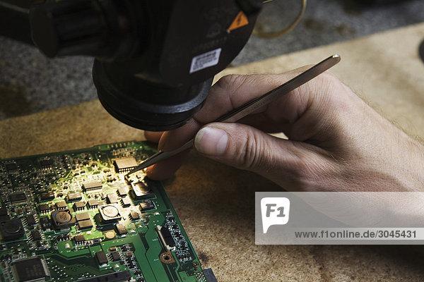 Nahaufnahme des Arbeitnehmers Hauptplatine Computers reparieren