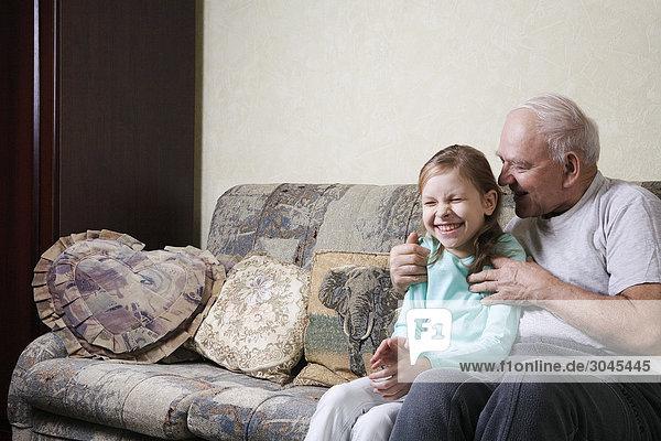 Großvater spielen mit jungen Mädchen auf sofa Großvater spielen mit jungen Mädchen auf sofa