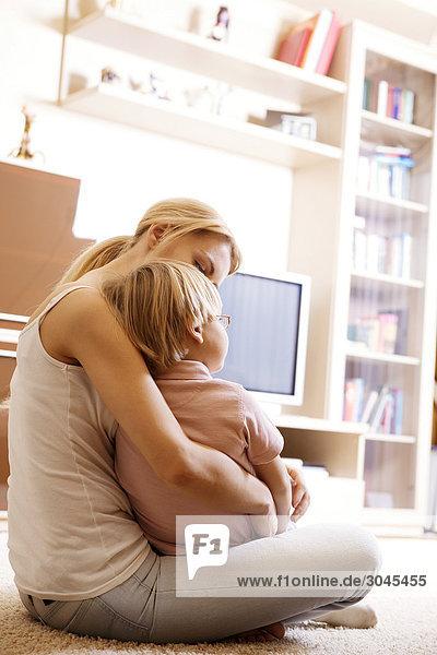 junge Mutter und ihr Sohn sitzen im Wohnzimmer im Erdgeschoss