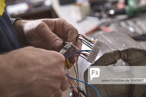 Nahaufnahme der Mechaniker schneiden Kabel mit Zangen Nahaufnahme der Mechaniker schneiden Kabel mit Zangen