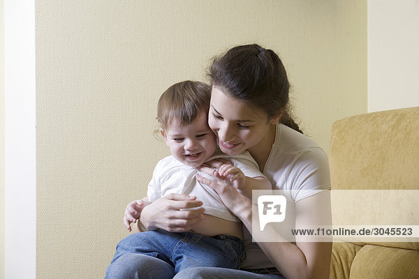 young mother sitting with her son on sofa