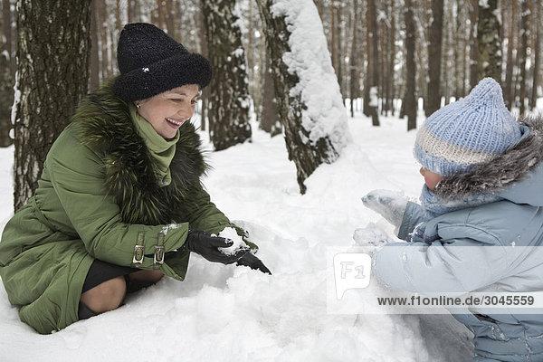 Großmutter und Young Girl playing with Snow zusammen