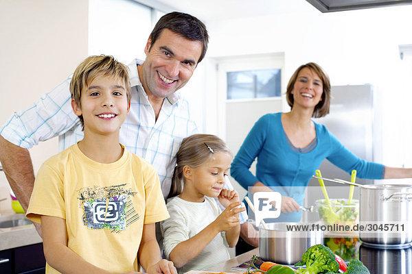 Eltern mit ihren Kindern in Küche kochen
