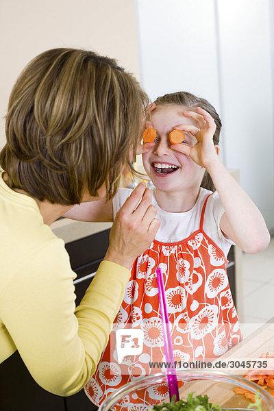 Mutter und Tochter Spaß mit Möhrenscheiben in Küche