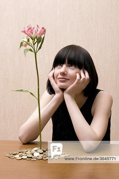 junge Frau betrachten von Haufen von Münzen wachsende Blume