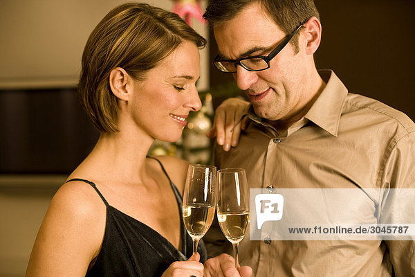 couple raising their glasses on christmas eve