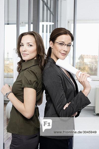 Porträt von zwei Geschäftsfrauen Rücken an Rücken stehend