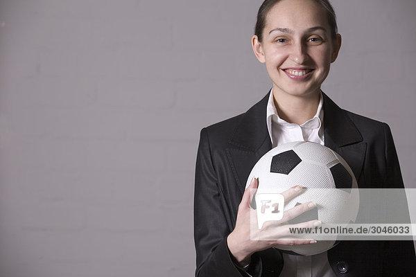 Porträt der jungen geschäftsfrau hält Fußball