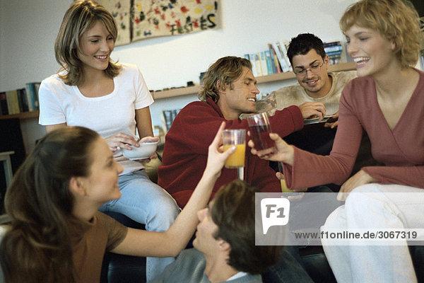 Zwei junge Frauen  die zu Hause anstoßen  treffen sich mit Freunden.