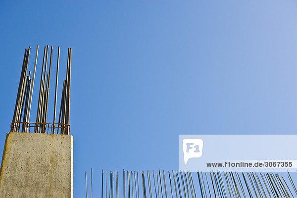Sichtbarer Bewehrungsstab  der aus der Rohbetonsäule gegen den blauen Himmel hervorsteht  Blickwinkel niedrig