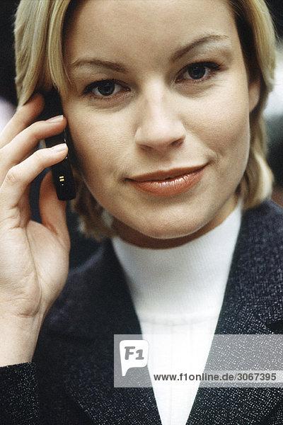 Frau telefoniert mit dem Handy und schaut optimistisch in die Kamera  Portrait