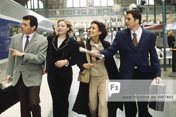 Geschäftsfreunde eilen gemeinsam den Bahnsteig hinunter auf der Suche nach einem Eisenbahnwaggon